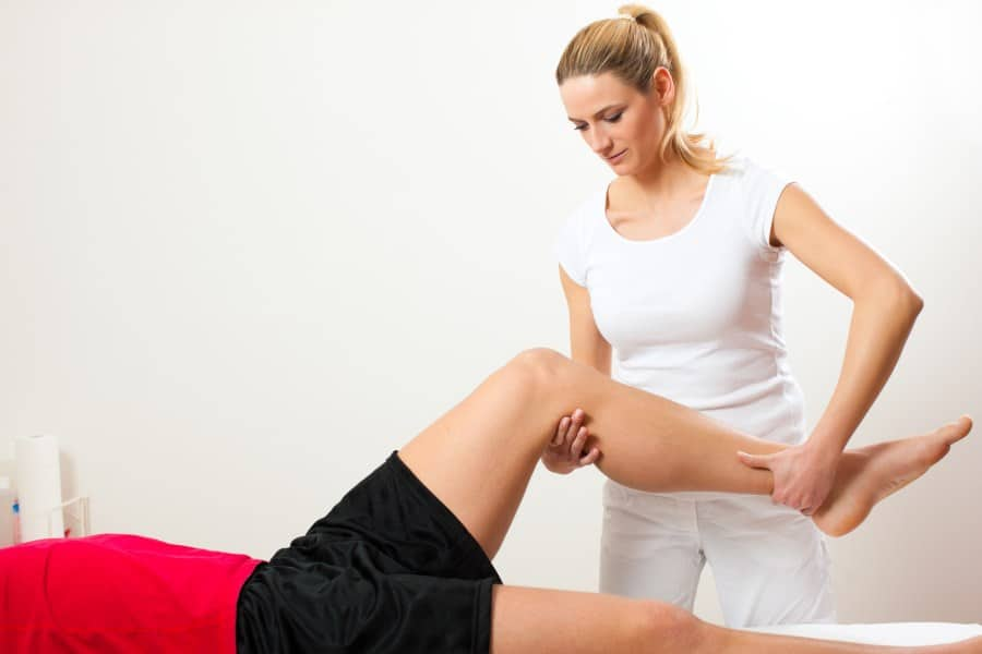 Physical therapist working on patients knee