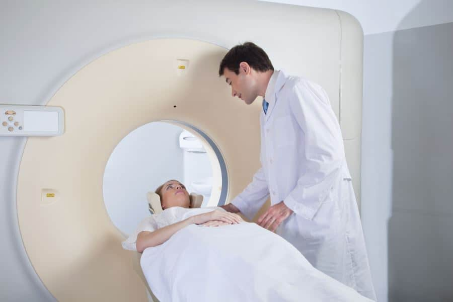 Radiation therapist helping patient